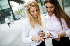 Picture of two young beautiful women as business partners. Standing outside Royalty Free Stock Image
