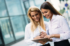 Picture of two young beautiful women as business partners. Standing outside Stock Photos