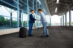 Picture of  two young businessmen meeting at background and shaking hands Royalty Free Stock Image