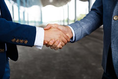 Picture of  two young businessmen on street background shaking hands Stock Images