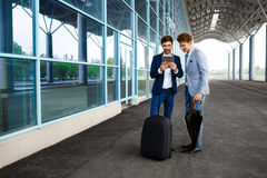 Picture of  two young businessmen talking on rainy station background and holding tablet Royalty Free Stock Images