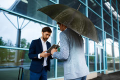 Picture of  two young businessmen talking at rainy station background Stock Photos