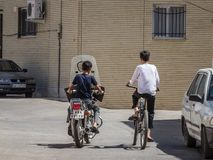 Two young boys, teenagers, riding a motocycle and a bicycle in the streets of the old Kashan, the main city of central Iran. Picture of two young teenager, boys stock photography