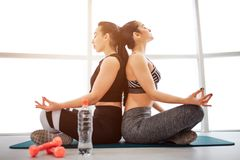 Picture of two young women sitting back to back in fintess room. They meditate with closed eyes. Models sit in lotus stock photo