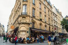 Cafe Bar Restaurant of the city center of Paris, during the afternoon, with people drinking in front of it during a happy hour. Picture of a typical street from royalty free stock images