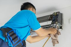 Unknown worker cleaning coil cooler of air conditioner. Picture of unknown male technician cleaning coil cooler of air conditioner, Shot at home Royalty Free Stock Photography