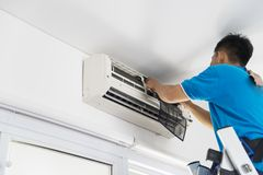 Unknown technician repairing an air conditioner. Picture of unknown male technician repairing an air conditioner at home Royalty Free Stock Photo