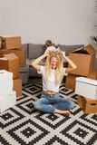 Picture of upset blonde woman sitting on floor among cardboard boxes and boy on gray sofa royalty free stock photography