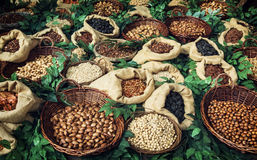 Picture of various kinds of nuts in wicker and burlap bowls Stock Photo