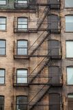 Fire escape stairs and ladder, in metal, on a typical North American old brick building from the Old Montreal, Quebec, Canada. Picture of vintage fire escape royalty free stock image