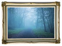 Picture in vintage frame. Mystical autumn forest with trail in blue fog. Beautiful landscape with trees, path, fog. Nature backgro royalty free stock images