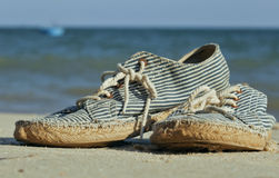 Picture of vintage old shabby sneakers at seacost Royalty Free Stock Photo