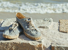 Picture of vintage old shabby sneakers at seacost Royalty Free Stock Image