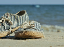 Picture of vintage old shabby sneakers at seacost Stock Images