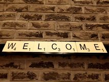Picture of a wall with the word welcome written with scrabble letters. stock photography