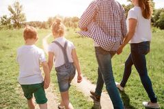 A picture that was made from the back. Happy family is walking together through meadow. Boy is holding hand of his stock photos