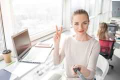 A picture that was made from a different angle where beautiful office worker is taking selfie and showing the piece stock photo