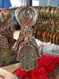 A Closeup On A Silver Key Holder In The Shape Of Arabic Hamsa Talisman With The Hebrew Word Alive Printed On It. The picture was taken in Carmel market, tel aviv Stock Photography