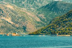 Fragment of Kotor Bay against the backdrop of the mountains and islands of Gospa with a small church and the Virgin of the rocks . royalty free stock photo