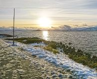 Beautiful September sunset at the snowy shores of a calm northern fjord in Norway. stock image