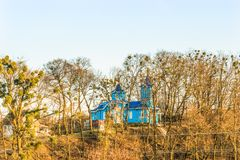 Beautiful rural church in the shade of tall trees. Royalty Free Stock Photos