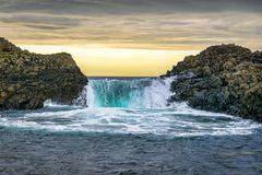This is a picture of a wave splashing over rocks at the sea at sunset royalty free stock photo
