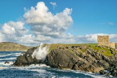 Waves Crashing onto Rocks. Picture of waves crashing on a rocky coast infront of a castle in Donegal Ireland royalty free stock photo