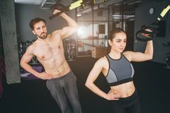 A picture of well-built and beautiful girl and boy holding a TRX loop and doing some stretching. They look serious and. Concentrated royalty free stock images