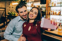 A picture where girl is making selfie with her boyfirend. THey are smiling and looking to the camera. THis couple is royalty free stock images