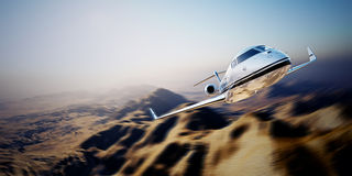Picture of white modern and luxury generic design private jet flying in blue sky over earth.Uninhabited desert mountain Royalty Free Stock Photo