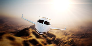Picture of white modern and luxury generic design private jet flying in blue sky at sunrise.Uninhabited desert mountain Stock Images