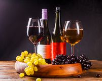 Picture of wine glass with wine, grapes black, green on wooden tray on table. In studio royalty free stock photography