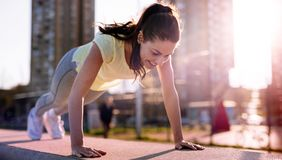 Picture of woman doing push ups in urban area stock photos