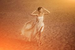 Woman in flying gold cloth. Picture of woman in flying gold cloth in the sand Royalty Free Stock Images