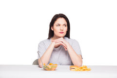 Picture of woman with fruits and hamburger in front on white bac. Kground, healthy versus junk food concept Royalty Free Stock Photos