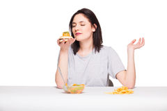 Picture of woman with fruits and hamburger in front on white bac Stock Photo
