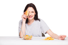 Picture of woman with fruits and hamburger in front on white bac Stock Image