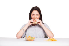 Picture of woman with fruits and hamburger in front on white bac. Healthy versus junk food concept with a natural woman heaving in front fruits meal and choosing Royalty Free Stock Photo