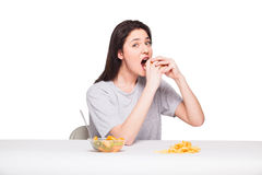 Picture of woman with fruits and hamburger in front on white bac. Healthy versus junk food concept with a natural woman heaving in front fruits meal and choosing Royalty Free Stock Photos