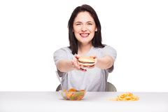Picture of woman with fruits and hamburger in front on white bac. Healthy versus junk food concept with a natural woman heaving in front fruits meal and choosing Stock Photography