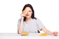 Picture of woman with fruits and hamburger in front on white bac. Healthy versus junk food concept with a natural woman heaving in front fruits meal and choosing Royalty Free Stock Images