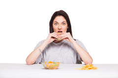 Picture of woman with fruits and hamburger in front on white bac. Healthy versus junk food concept with a natural woman heaving in front fruits meal and choosing Stock Photo