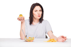 Picture of woman with fruits and hamburger in front on white bac Royalty Free Stock Images