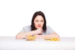 Picture of woman with fruits and hamburger in front on white bac. Healthy versus junk food concept with a natural woman heaving in front fruits meal and fries Stock Image