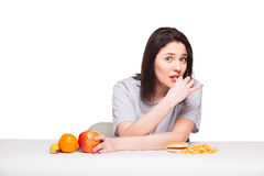 Picture of woman with fruits and hamburger in front on white bac. Healthy versus junk food concept with a natural woman heaving in front fruits meal and fries Stock Photography
