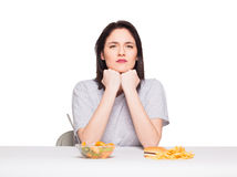 Picture of woman with fruits and hamburger in front on white bac. Healthy versus junk food concept with a natural woman heaving in front fruits meal and fries Royalty Free Stock Photos