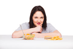 Picture of woman with fruits and hamburger in front on white bac. Healthy versus junk food concept with a natural woman heaving in front fruits meal and fries Stock Photo