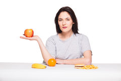 Picture of woman with fruits and hamburger in front on white bac. Healthy versus junk food concept with a natural woman heaving in front fruits meal and fries Royalty Free Stock Photo