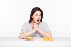 Picture of woman with fruits and hamburger in front on white bac. Healthy versus junk food concept with a natural woman heaving in front fruits meal and fries Royalty Free Stock Images