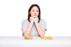 Picture of woman with fruits and hamburger in front on white bac Stock Photography